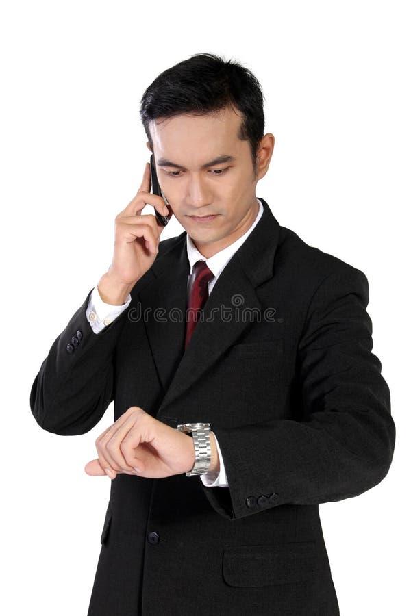Homme d'affaires au téléphone vérifiant à sa montre, d'isolement sur le blanc photo libre de droits