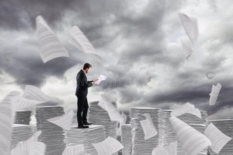 Homme d'affaires au travail au-dessus d'une pile des tours de papier des fiches de travail photographie stock