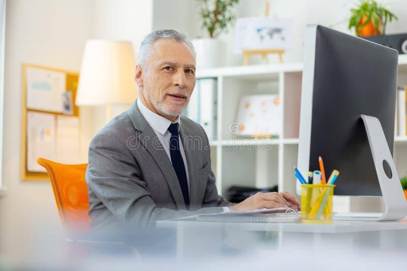 Homme d'affaires aux cheveux courts curieux seul s'asseyant dans le bureau photographie stock