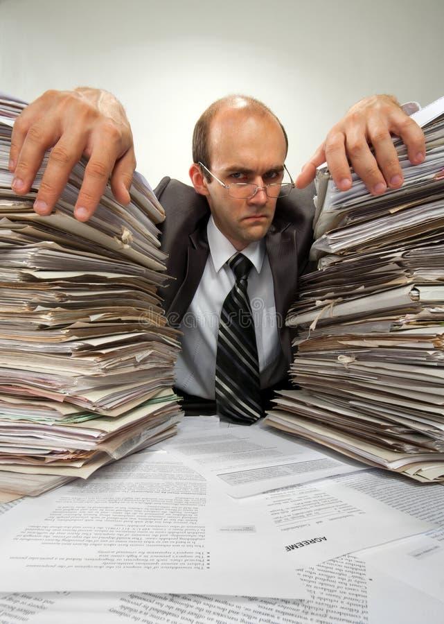 Homme d'affaires avec de grandes piles des écritures images stock
