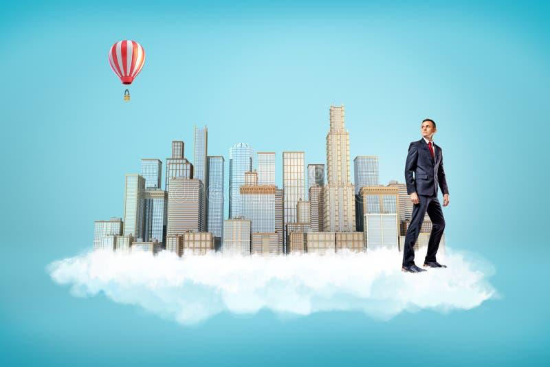 Homme d'affaires avec des gratte-ciel de ville sur le nuage blanc et le ballon à air chaud dans le ciel sur le fond bleu image libre de droits