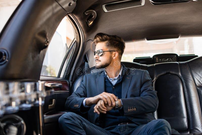 Homme d'affaires avec des nuances dans la limousine image libre de droits
