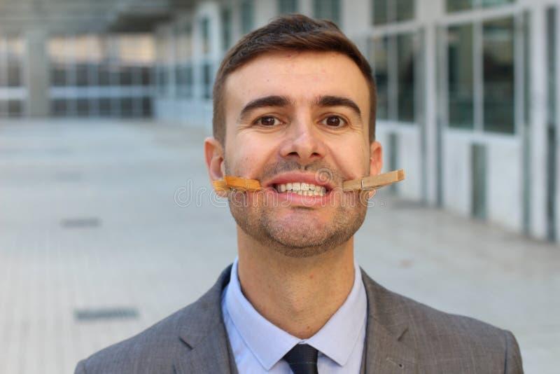 Homme d'affaires avec des pinces à linge créant un faux sourire images libres de droits