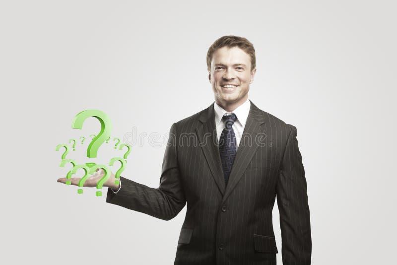 Homme d'affaires avec des points d'interrogation sur sa main image stock