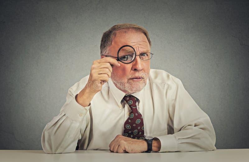 Homme d'affaires avec des verres vous regardant avec scepticisme images stock
