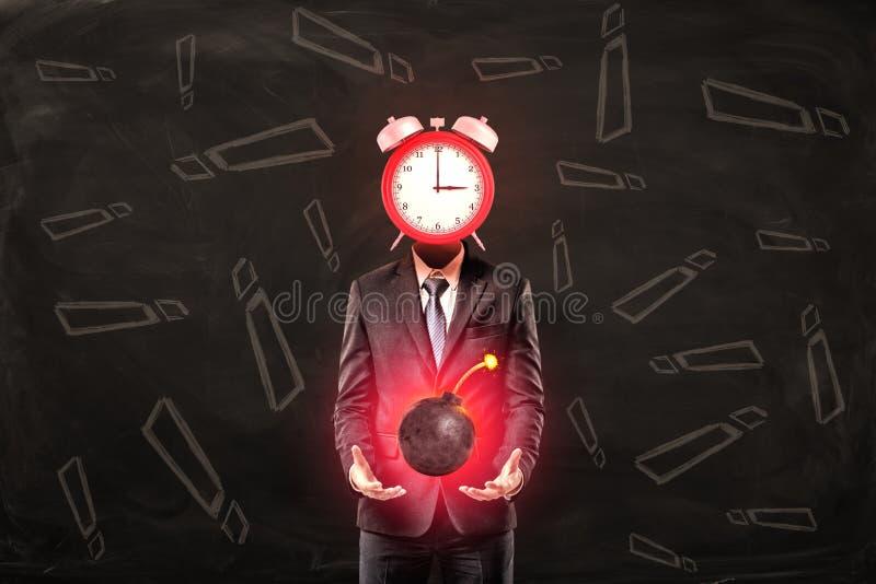 Homme d'affaires avec l'horloge au lieu de la bombe de boule de participation de tête avec le fusible sur le fond noir avec le mo images stock