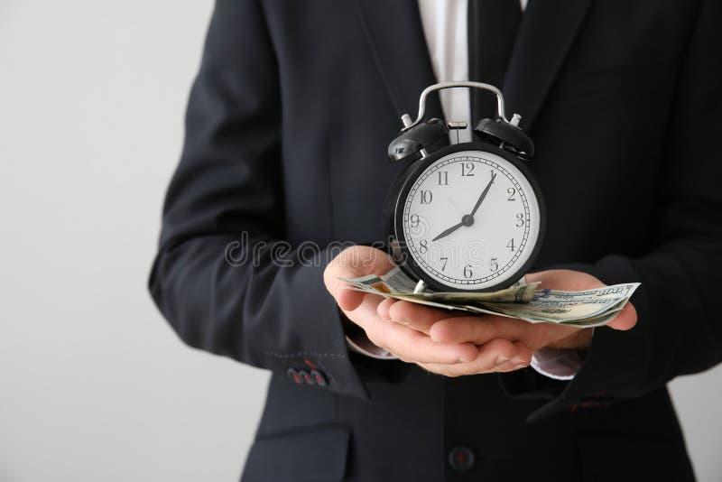 Homme d'affaires avec l'horloge et l'argent sur le fond clair, plan rapproché photographie stock libre de droits