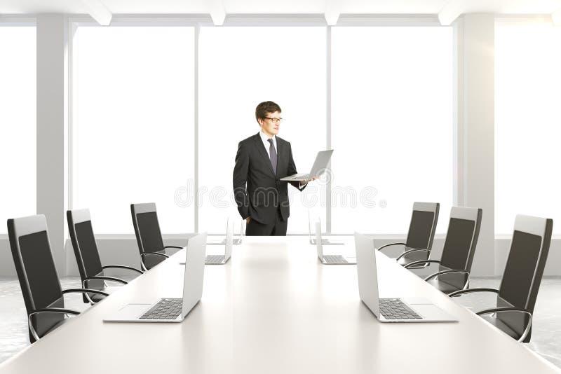 Homme d'affaires avec l'ordinateur portable dans la salle de conférence blanche moderne avec l'étiquette images stock