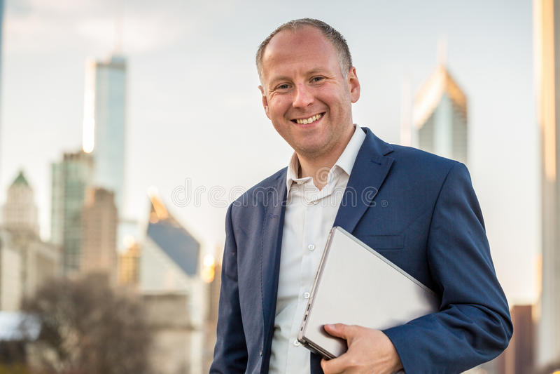 Homme d'affaires avec l'ordinateur portable devant des immeubles de bureaux image libre de droits