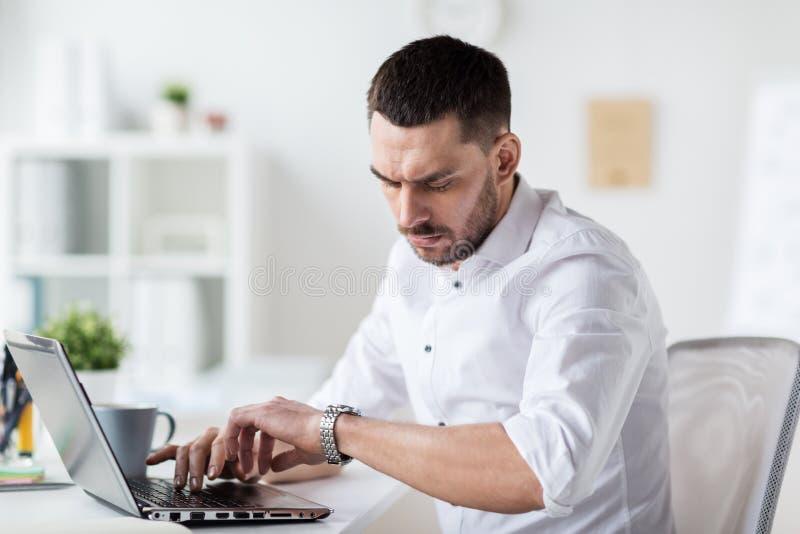 Homme d'affaires avec l'ordinateur portable et la montre-bracelet au bureau images libres de droits