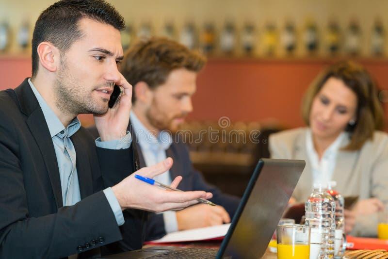 Homme d'affaires avec l'ordinateur portable et le téléphone portable en café images libres de droits