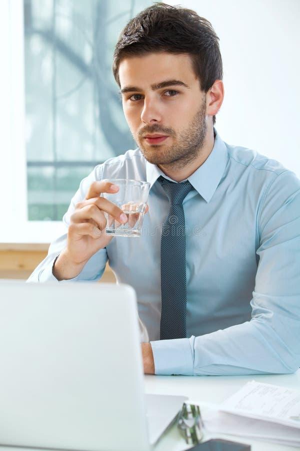 Homme d'affaires avec l'ordinateur portable fonctionnant dans le bureau image stock