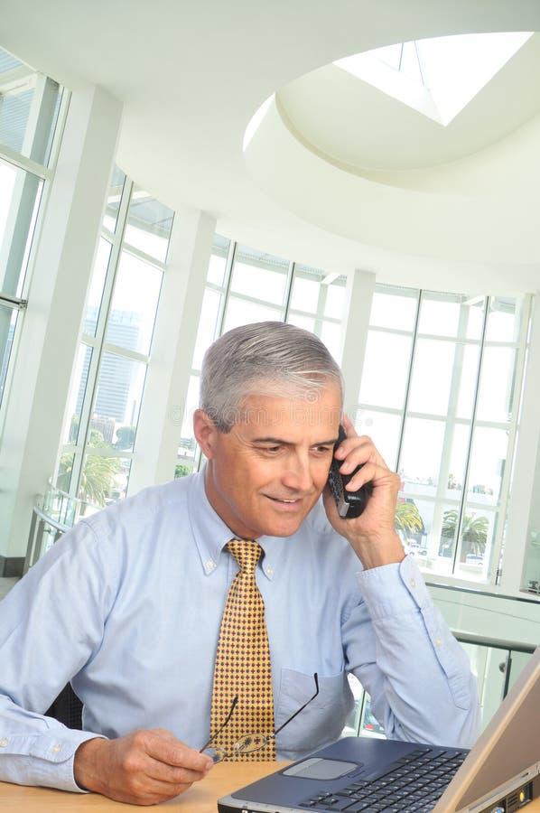 Homme d'affaires avec l'ordinateur portatif et le téléphone photos stock