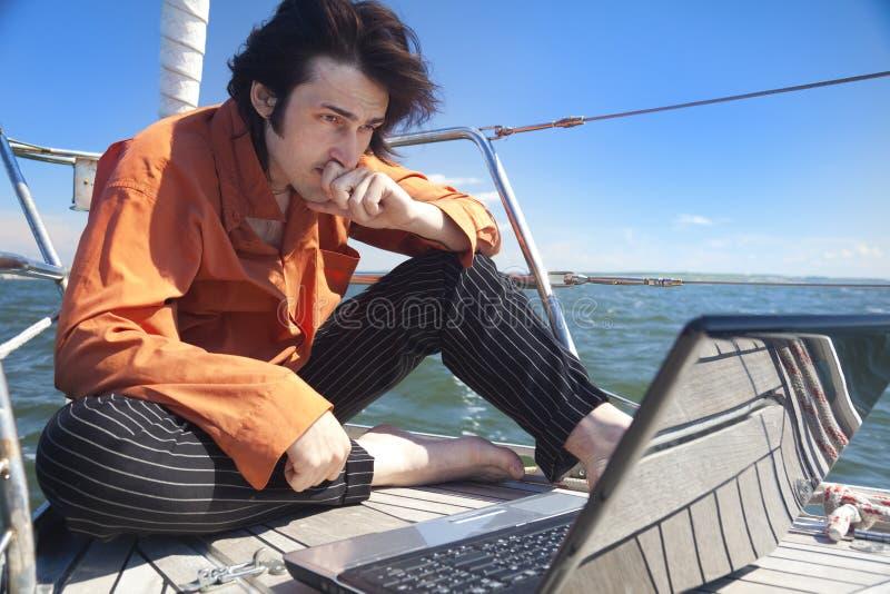 Homme d'affaires avec l'ordinateur portatif sur le bateau à voiles photos stock