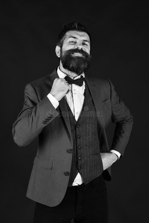 Homme d'affaires avec la barbe ajustant son noeud papillon photo stock