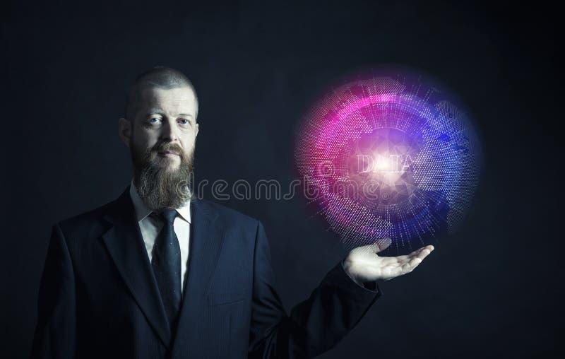 Homme d'affaires avec la barbe sur le fond noir dans le costume noir tenant la boule le concept de grandes données dans la terre photos libres de droits