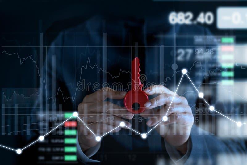 Homme d'affaires avec la clé rouge pour le succès dans des mains sur le fond coloré de marché boursier de diagrammes et de diagra image libre de droits