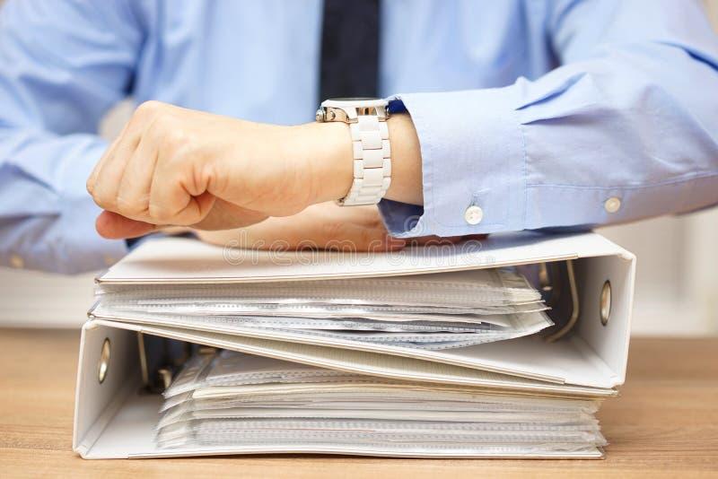 Homme d'affaires avec la pile de documentation sur le bureau regardant sur W image stock