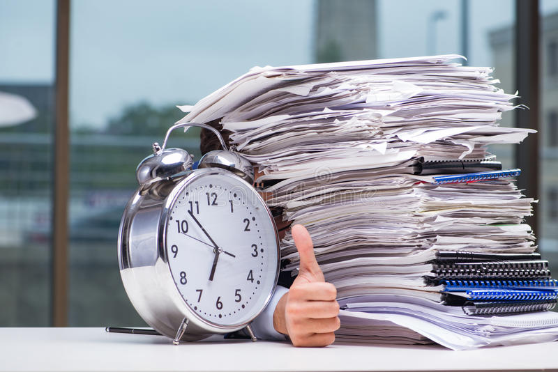 Homme d'affaires avec la pile de pile d'écritures de papier et d'un cloc d'alarme photos stock