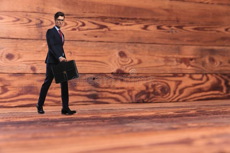Homme d'affaires avec la serviette marchant sur le vieux fond en bois images libres de droits
