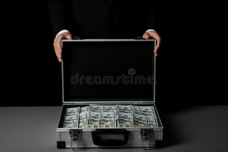 Homme d'affaires avec la valise pleine de l'argent photos stock