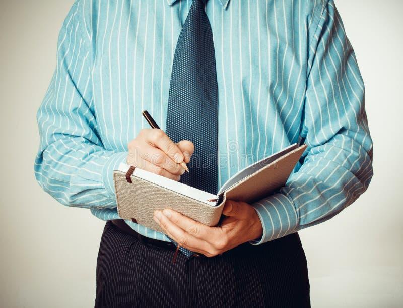 Homme d'affaires avec le carnet et l'écriture de crayon lecteur photographie stock