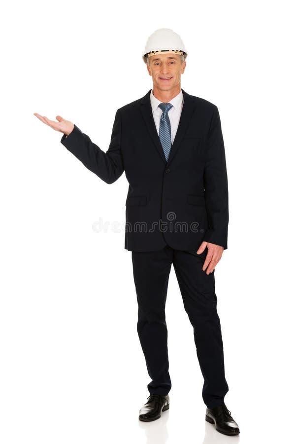 Homme d'affaires avec le casque antichoc tenant le copyspace photos stock