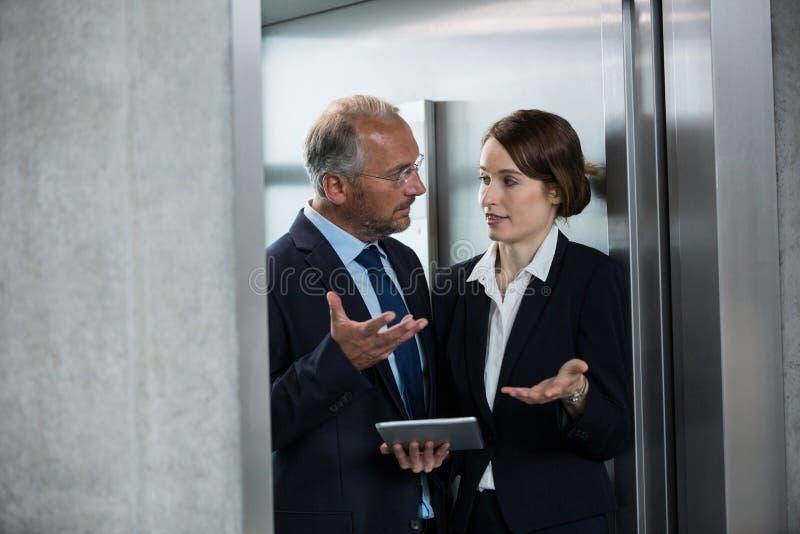 Homme d'affaires avec le collègue dans un ascenseur image stock