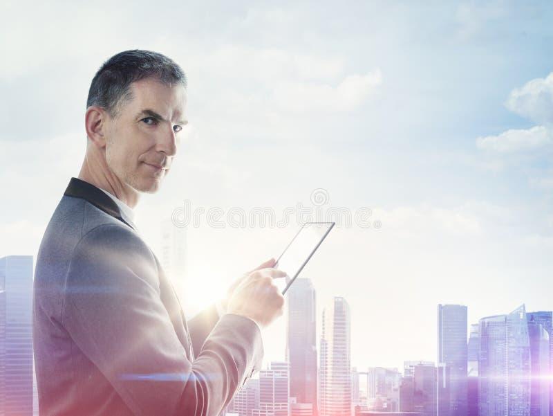 Homme d'affaires avec le comprimé numérique et ville brouillée sur l'horizon photo stock