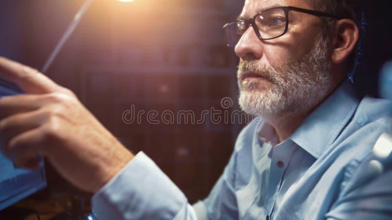 Homme d'affaires avec le fonctionnement en verre focalisé dans le bureau la nuit image libre de droits