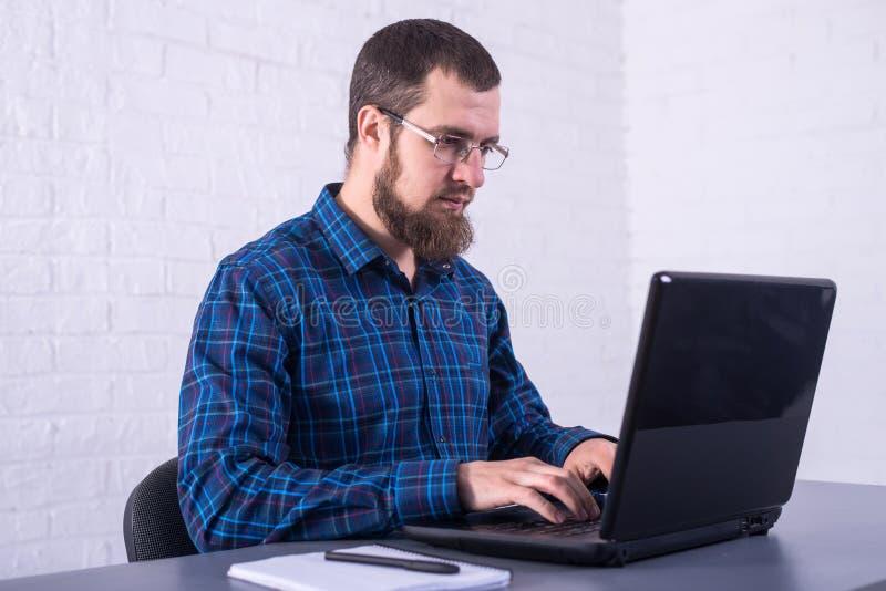 Homme d'affaires avec le fonctionnement en verre sur un ordinateur portable images stock