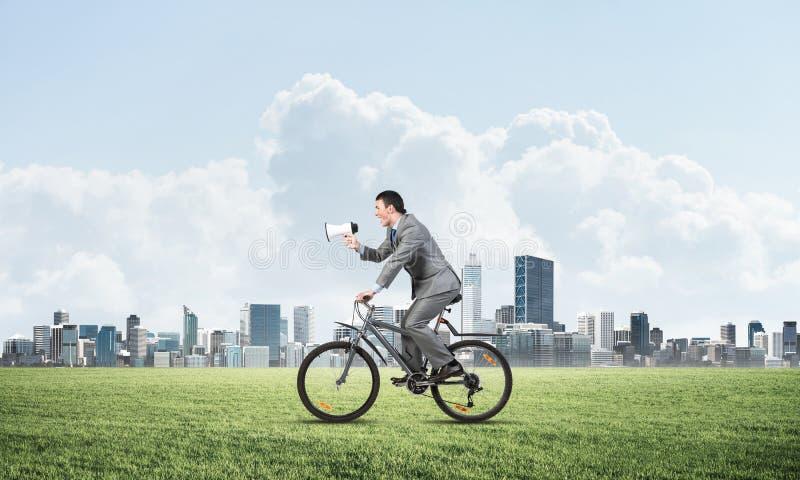 Homme d'affaires avec le mégaphone sur le vélo image libre de droits