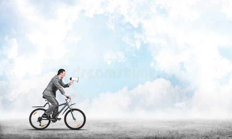 Homme d'affaires avec le mégaphone sur le vélo photographie stock libre de droits