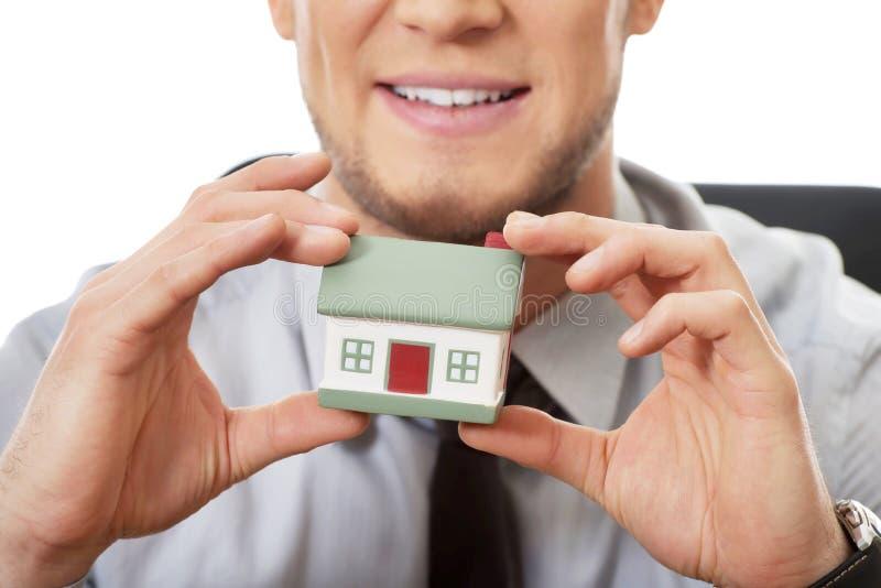 Homme d'affaires avec le modèle de maison par un bureau photographie stock