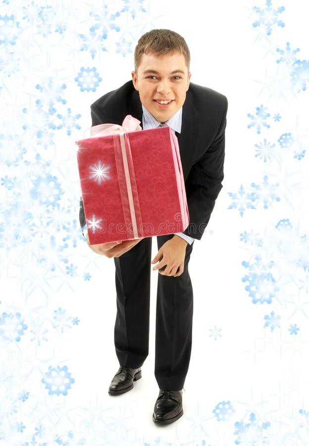 Homme d'affaires avec le paquet et les flocons de neige roses de cadeau photos stock