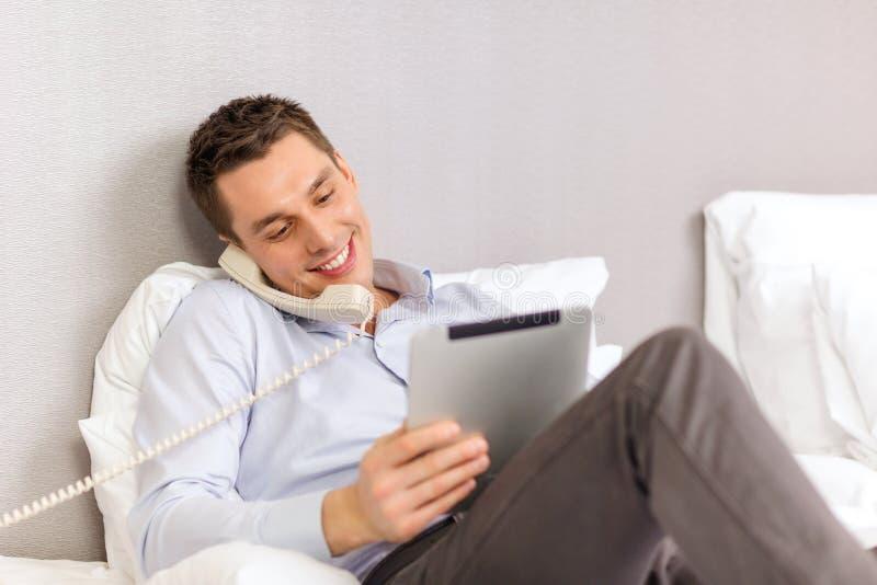Homme d'affaires avec le PC et le téléphone de comprimé dans la chambre d'hôtel images stock