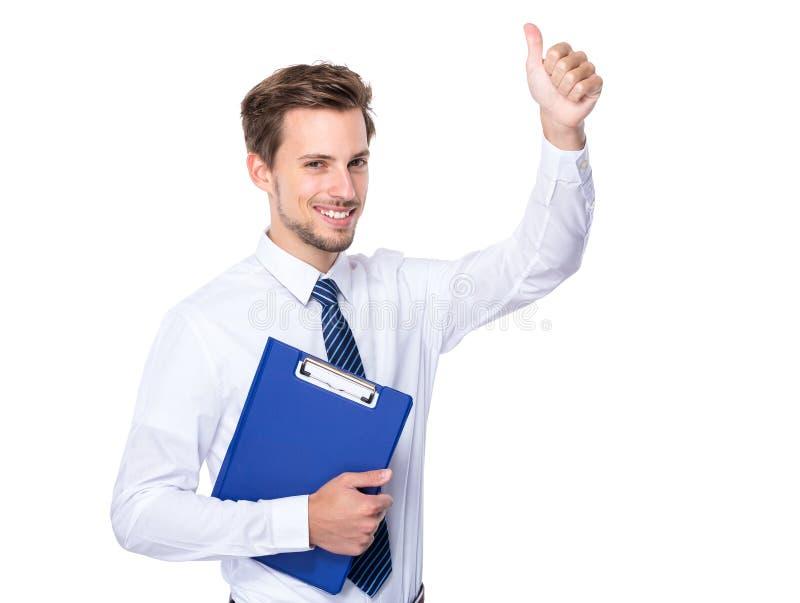 Homme d'affaires avec le presse-papiers et le pouce  image libre de droits