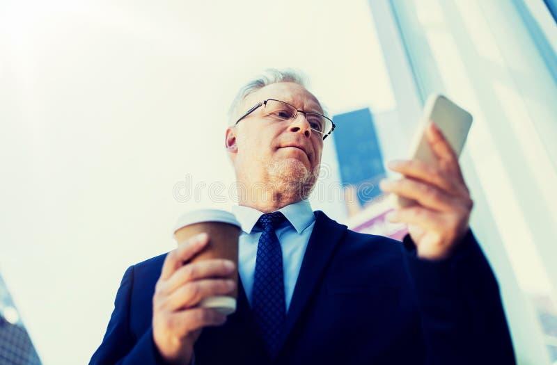 Homme d'affaires avec le smartphone et le caf? dans la ville photos stock