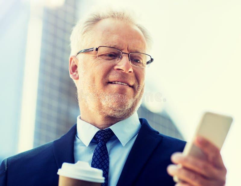 Homme d'affaires avec le smartphone et le caf? dans la ville images stock