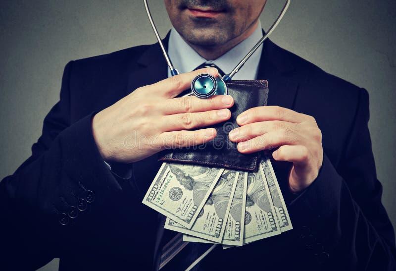 Homme d'affaires avec le stéthoscope écoutant le portefeuille avec des billets de banque du dollar image stock