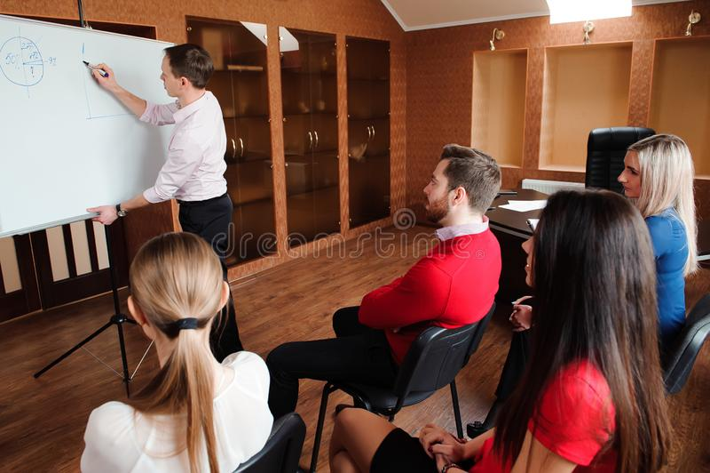 Homme d'affaires avec son personnel, groupe de personnes à l'arrière-plan au bureau lumineux moderne à l'intérieur photo libre de droits
