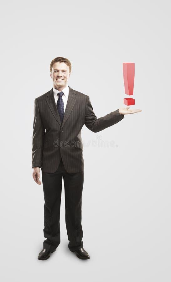 Homme d'affaires avec un repère d'exclamation sur sa main photo stock