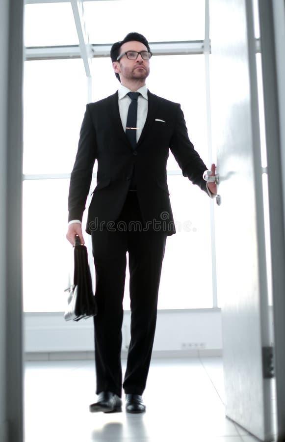 Homme d'affaires avec une serviette en cuir entrant dans son bureau du ` s de client image stock