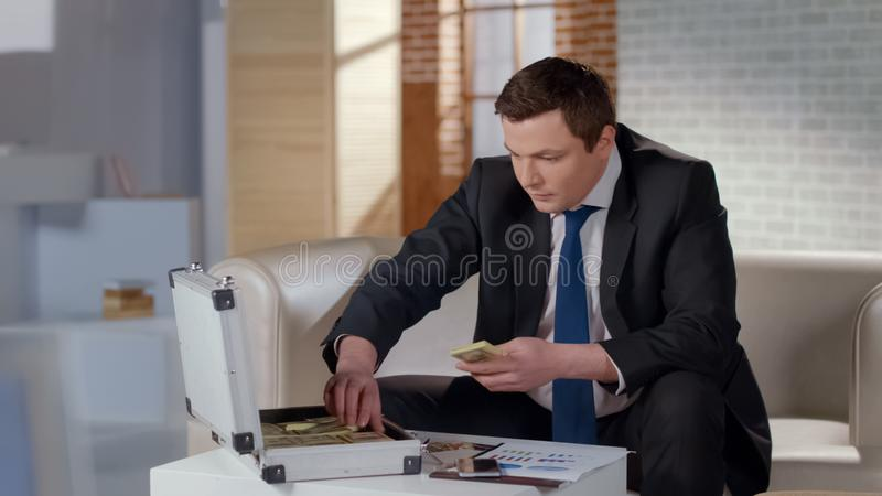 Homme d'affaires avide comptant l'argent dans la serviette, célébrant le démarrage rentable photos stock