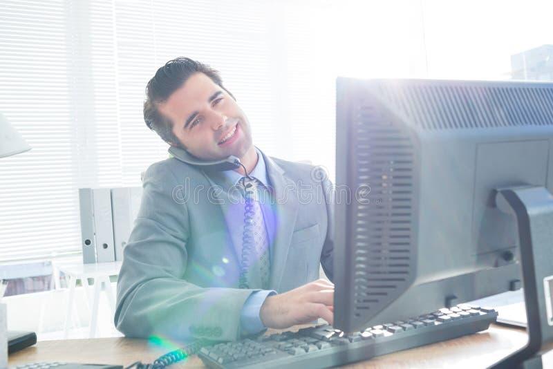 Download Homme D'affaires Ayant L'appel Téléphonique Tout En à L'aide De Son Ordinateur Photo stock - Image du mâle, jour: 56482792