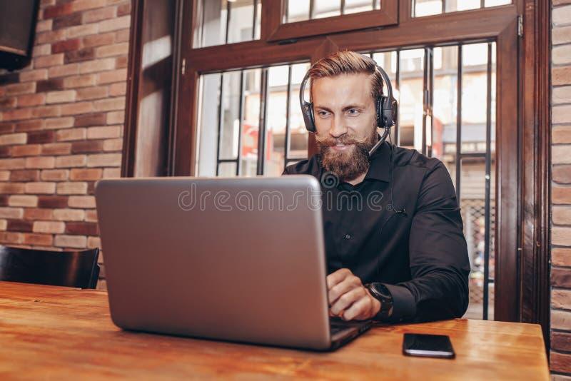 Homme d'affaires barbu avec le fonctionnement de casque avec l'ordinateur portable photos stock
