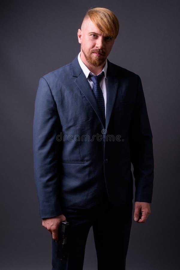 Homme d'affaires barbu avec le pistolet sur le fond gris image libre de droits