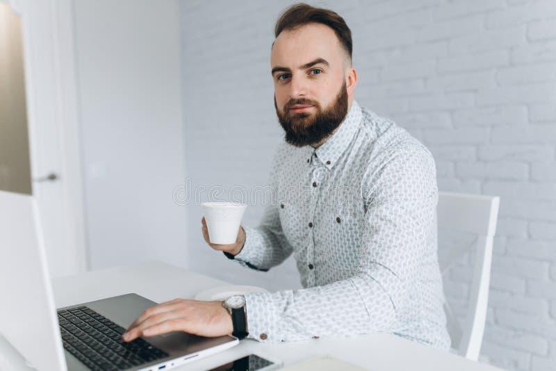 Homme d'affaires barbu bel travaillant avec l'ordinateur portable dans le bureau, le café potable et la relaxation photographie stock