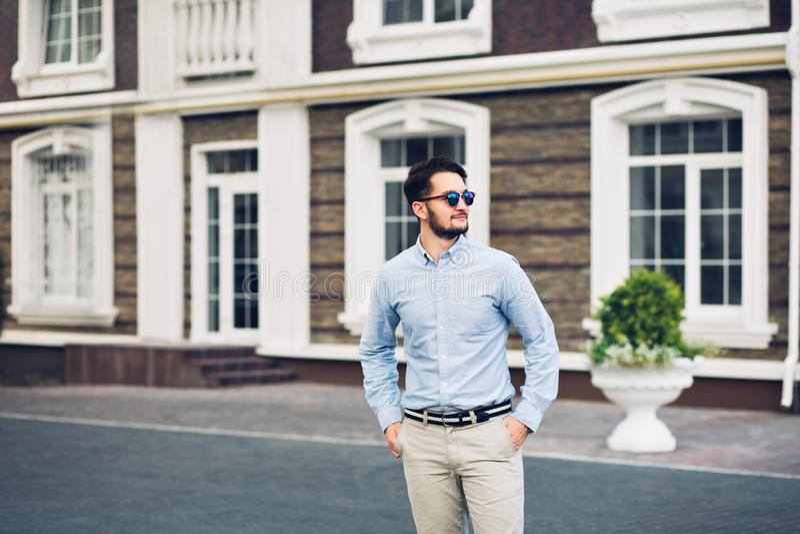 Homme d'affaires barbu dans des lunettes de soleil marchant sur la rue Il tient des mains dans des poches, souriant loin photographie stock