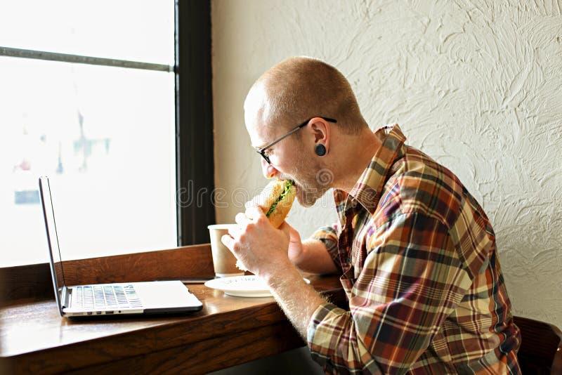 Homme d'affaires barbu de sourire portant l'habillement occasionnel de hippie utilisant le smartphone d'ordinateur portable et de photographie stock libre de droits